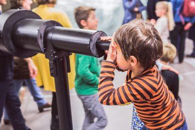 kind kijkt door verrekijker op stormopkomst in de warande